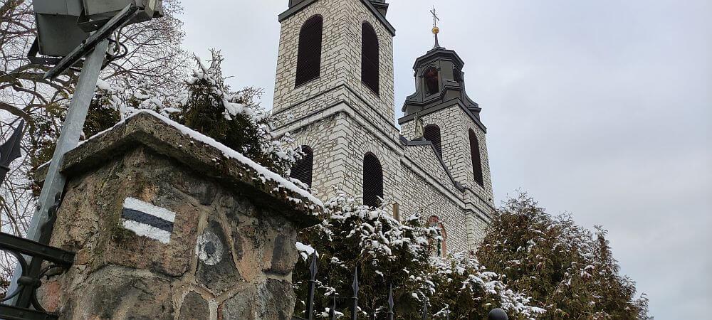 Stare oznaczenie początku Szlaku Kroczyckiego przy kościele w Kroczycach